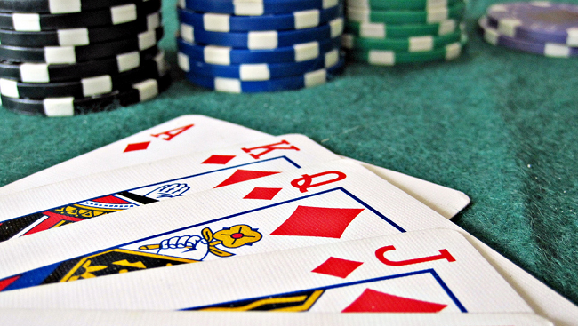 A photo featuring a close up shot of red playing cards; an Ace, King, Queen and Jack, as well as stacks of poker chips.