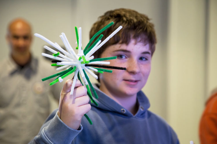 A student at a Brain Awareness event shows off his neuron model.
