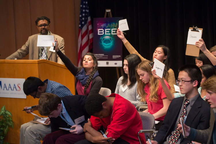 Students show their answers to a question during a Brain Bee.