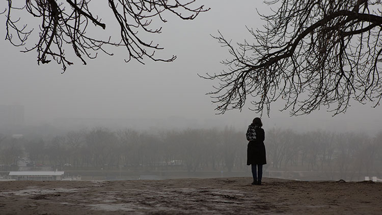 Person standing under tree in gloomy weather