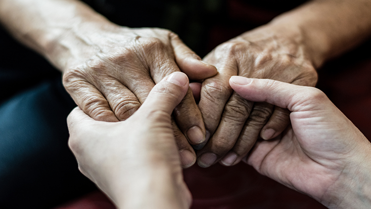 Young hands holding older person's hands