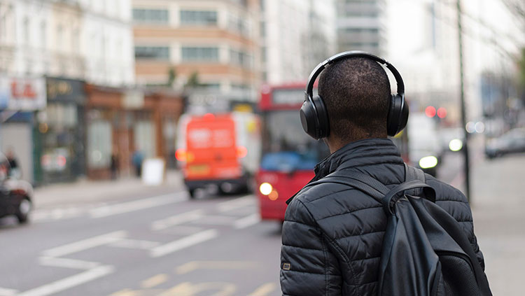 man in the city with his back turned wearing headphones