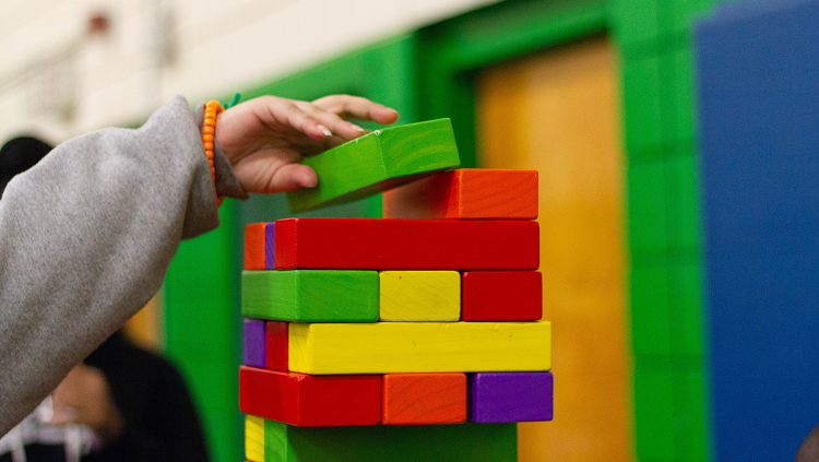 young child building with colorful wooden blocks
