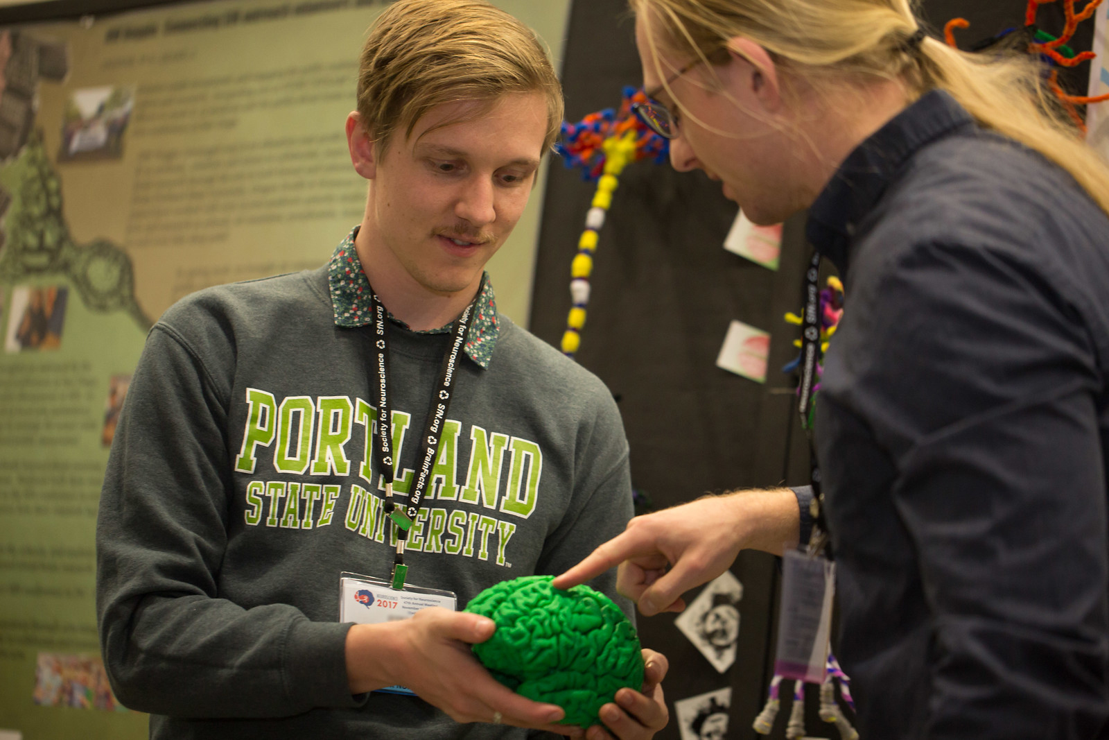 a person holding out a scientific brain model as another person touches the model