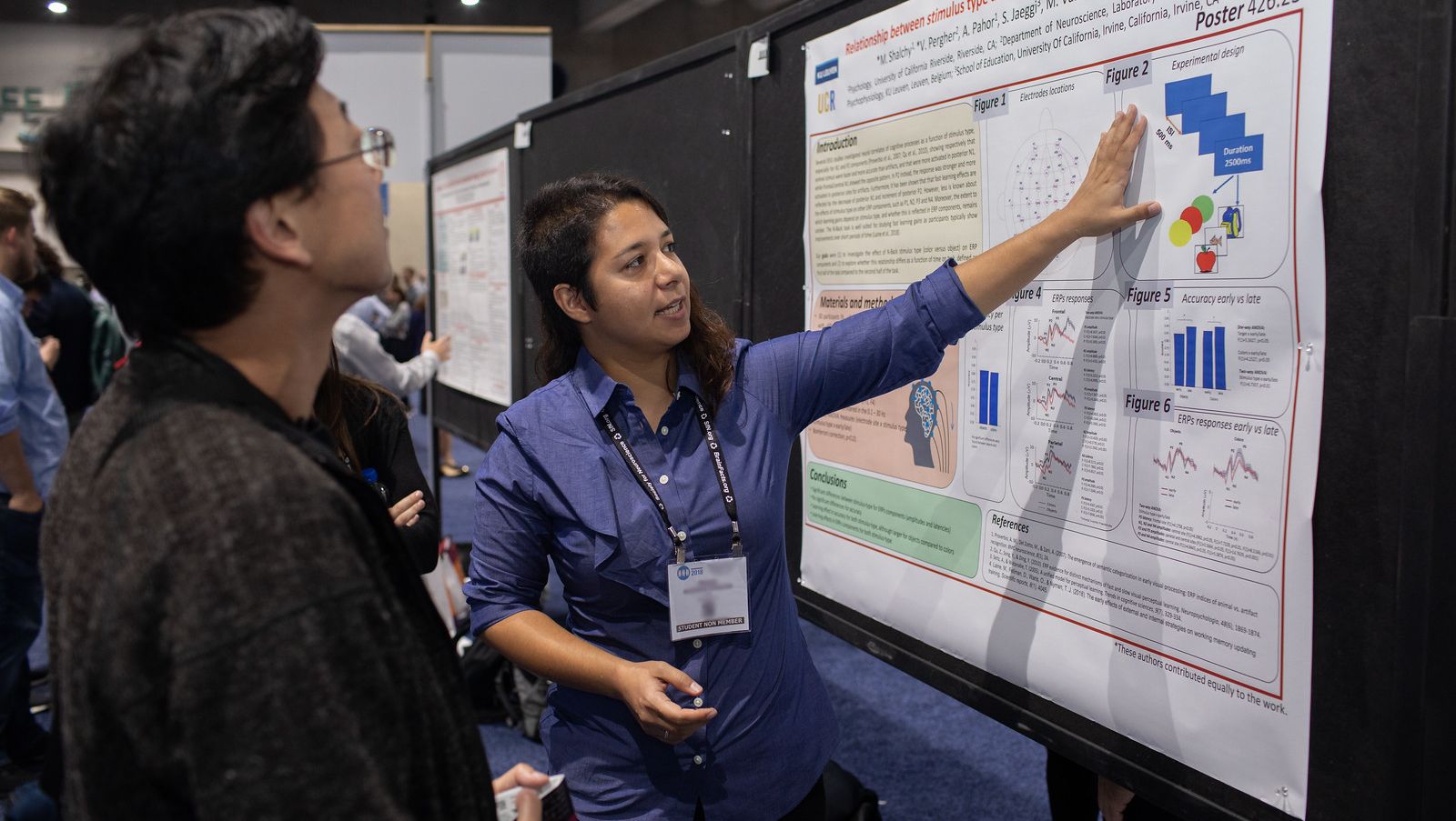One Neuroscience 2018 attendee explaining poster presentation to another attendee