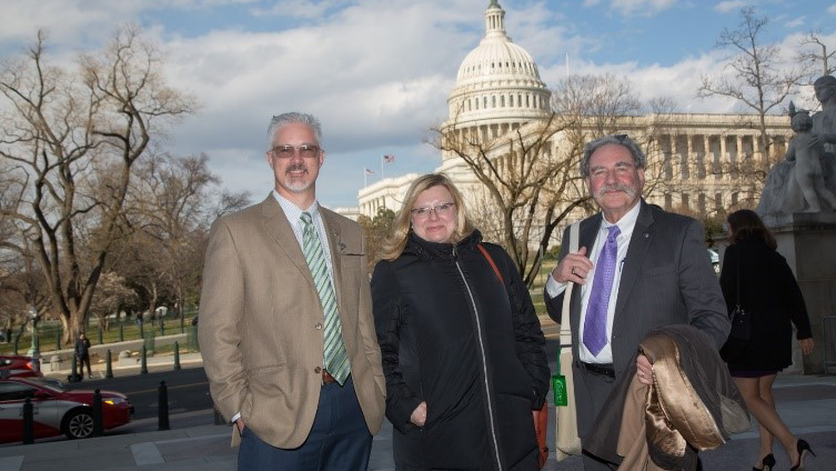 Three NeuroAdvocates pose in front of the US Capitol building