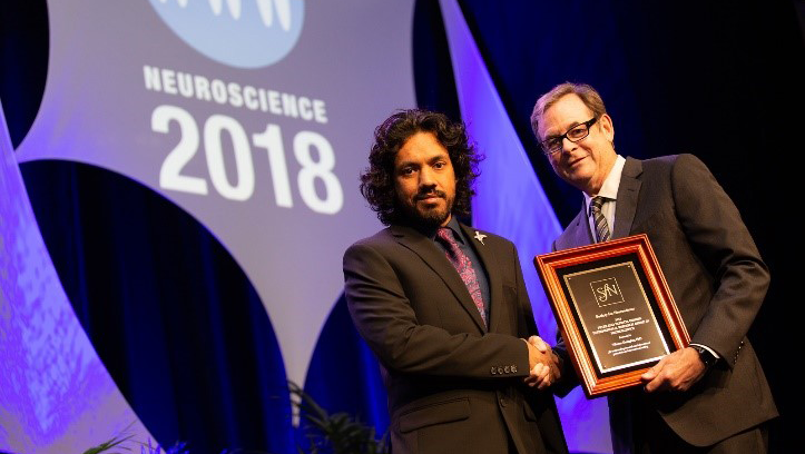 Vikram Gadagkar (left), PhD, of Cornell University, accepts the Peter and Patricia Gruber International Research Award from SfN President Richard Huganir