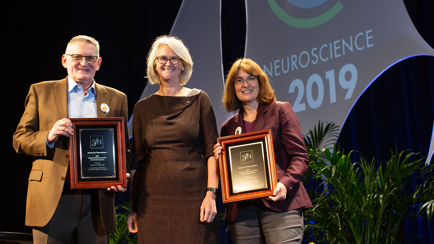 Robert T. Knight, MD (right), of the University of California, Berkeley, and Sabine Kastner, MD, PhD (left), of Princeton University, accept the Award for Education in Neuroscience