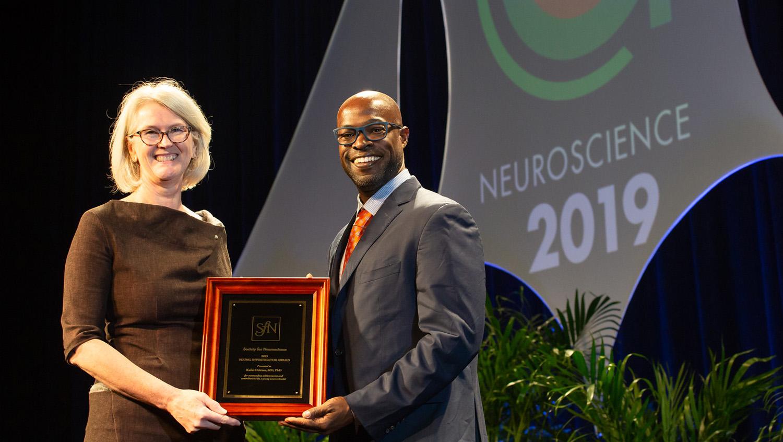 Kafui Dzirasa, MD, PhD (right), of Duke University, receives the Young Investigator Award
