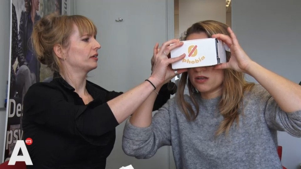 Tara Donker, left, fits a patient with ZeroPhobia's virtual reality goggles for the treatment of the fear of heights. Donker is completeing research into the effectivenes of ZeroPhobia for the fear of flying.